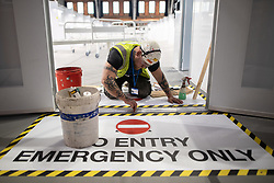 © Licensed to London News Pictures. 12/04/2020. Manchester, UK. Mastic man ANDREW ROBINSON (38) sealing up door strips . The National Health Service is building a 648 bed field hospital for the treatment of Covid-19 patients , at the historical railway station terminus which now forms the main hall of the Manchester Central Convention Centre . The facility is due to open on Easter Monday , 13th April 2020 , and will treat patients from across the North West of England , providing them with general medical care and oxygen therapy after discharge from Intensive Care Units . Photo credit: Joel Goodman/LNP