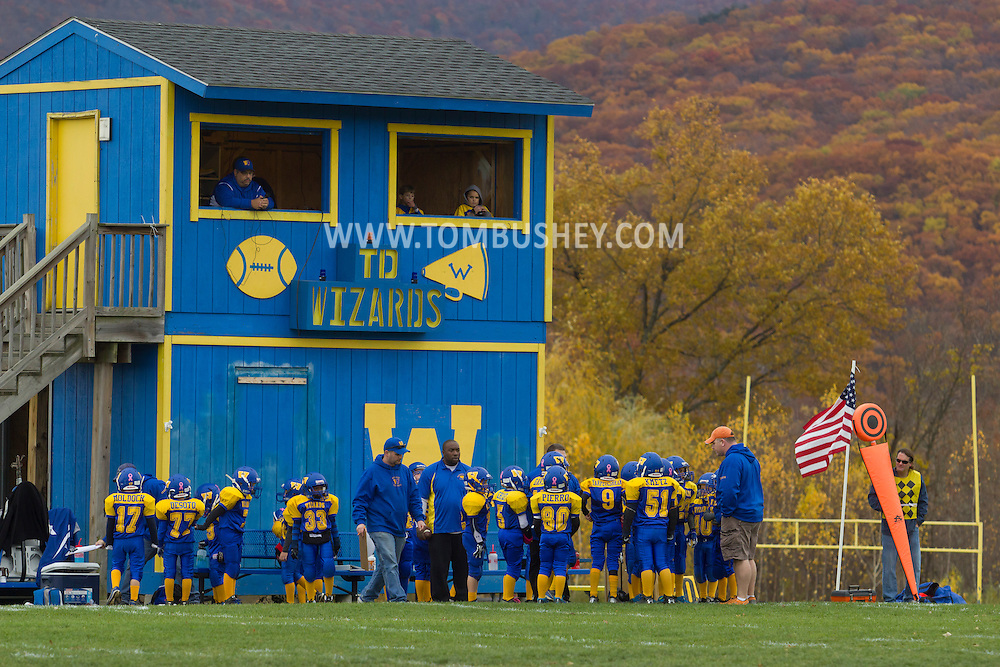 Salisbury Mills, New York  - Washingtonville Gold players and coaches gather on the sideline before the start of the second half of an Orange County Youth Football League Division I playoff game against Middletown at Lasser Field on Sunday, Nov. 3, 2013.