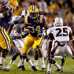 November 13, 2010; Baton Rouge, LA, USA; LSU Tigers running back Stevan Ridley (34) runs as Louisiana Monroe Warhawks safety Isaiah Newsome (25) pursues the play during the first half at Tiger Stadium.  Mandatory Credit: Derick E. Hingle