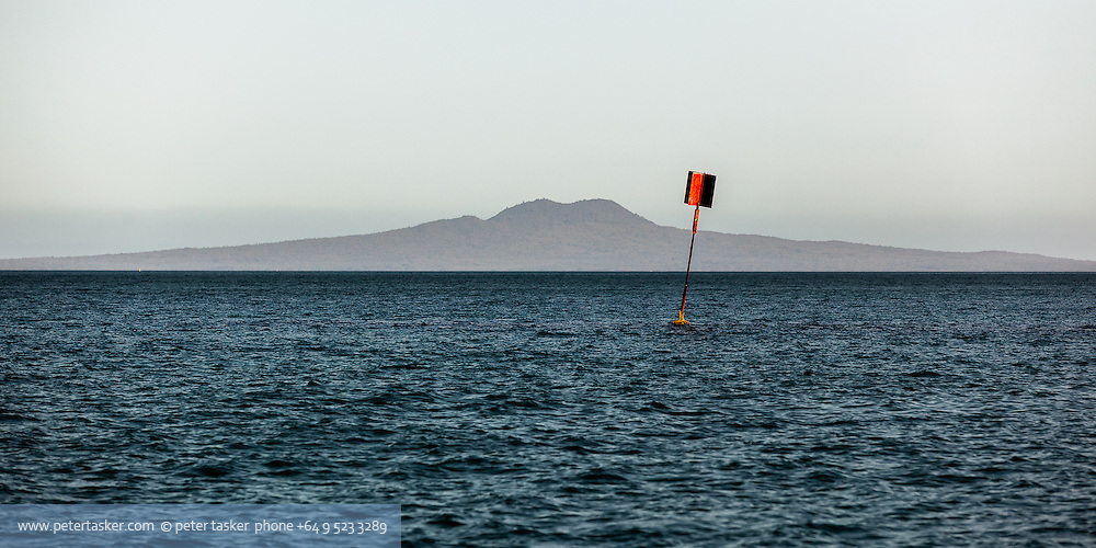 A spindly port marker buoy with Rangitoto Island behind. Simply red and blue.