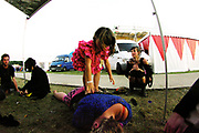 A child balances on a woman's back,  Boomtown, Matterley Estate, Alresford Road, Winchester, Hampshire, UK, August, 2010
