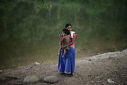61139418<br /> A girl of the Ngabe Bugle ethnic group A woman of the Ngabe Bugle ethnic group carries her baby in a camp near the Tabasara river bank in the Ngabe Bugle indigenous region, 450 km west of Panama City, capital of Panama, on Feb. 24, 2014. The Ngabe Bugle indigenous region is located in the western region of Panama, and covers an area of 6,968 square km, with 91 per cent of its population living in extreme poverty. Native leaders of the Ngabe Bugle region declared a national alert , because of the eviction notice issued by a company which is developing the hydro-electric project Barro Blanco . The project will use the water from Tabasara river in Chiriqui province, which will permanently flood nearly six hectares that contain native dwellings,  Monday, 24th February 2014. Picture by  imago / i-Images<br /> UK ONLY