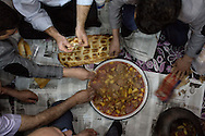 Staff at a textile shop in Van sit down to a firin-cooked lunch. Several hours earlier the shop's owner mixed meat, potatoes and chilies in a pot and sent it off to a nearby firin to cook. It returned to the shop to eat with fresh pide.
