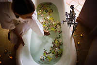 A woman fills a bathtub in her luxury hotel resort villa.