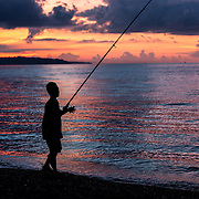 INDONESIA, Amed, Bali. May 25th, 2014.  A local fisherman fishes along the coast, enjoying a nice quiet sunset off the beach. Amed lies on the north-east tip of Bali and its beach is a long stretch of coast, famous for its glistening black sand, tranquility and stunning sunset views.