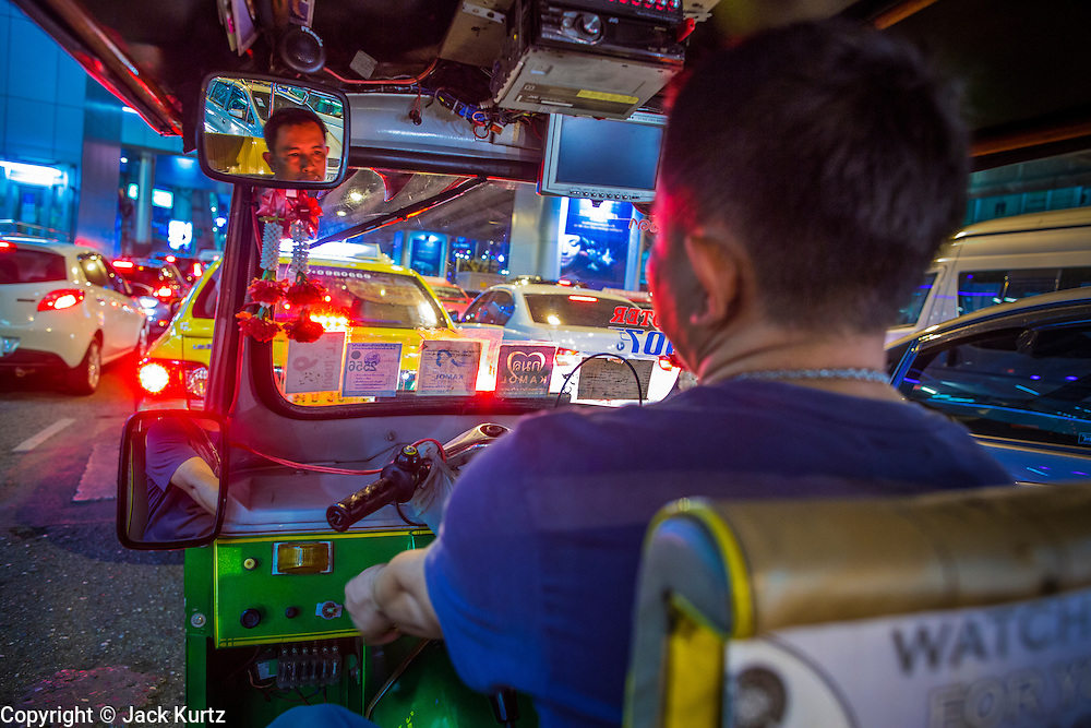 "12 JANUARY 2013 - BANGKOK, THAILAND:  A tuk-tuk driver on Sukhmvit Road between the red light districts of Nana and Soi Cowboy. Prostitution in Thailand is illegal, although in practice it is tolerated and partly regulated. Prostitution is practiced openly throughout the country. The number of prostitutes is difficult to determine, estimates vary widely. Since the Vietnam War, Thailand has gained international notoriety among travelers from many countries as a sex tourism destination. One estimate published in 2003 placed the trade at US$ 4.3 billion per year or about three percent of the Thai economy. It has been suggested that at least 10% of tourist dollars may be spent on the sex trade. According to a 2001 report by the World Health Organisation: ""There are between 150,000 and 200,000 sex workers (in Thailand).""    PHOTO BY JACK KURTZ"