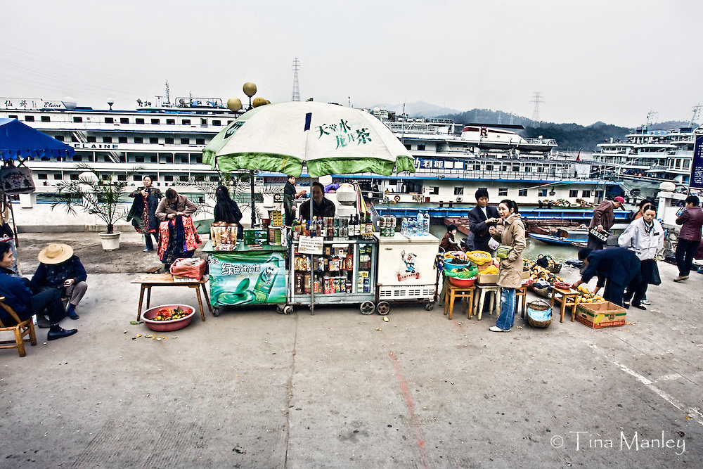CHINA, SANDOUPING:  Vendors selling souvenirs, snack, wine and books about the Three Gorges Dam meet the cruise ships that stop at Sandouping and the Three Gorges Dam during a Yangtze River Cruise. Photo Illustration.
