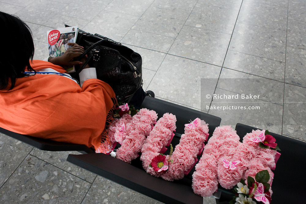 "We look down behind an airline passenger who is alone on seating in the departures concourse of Heathrow Airport's Terminal 5. Mourning the death of a mother, the lady sits with a floral tribute to the recently-deceased relative whose name 'Mum' is laid out next to her in pink flowers. On her lap is the organic Soil Association's magazine Living Earth. Perhaps the woman is on her way to a family funeral and is flying from T5 on this sad flight. Amid the otherwise bustling international airport, the woman seeks solace and tries to sleep before her check-in zone opens. From writer Alain de Botton's book project ""A Week at the Airport: A Heathrow Diary"" (2009). ."