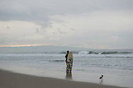 Surfer watching the waves at the Santa Monica Beach on a cloudy morning with two birds. Santa Monica, CA 11.30.14
