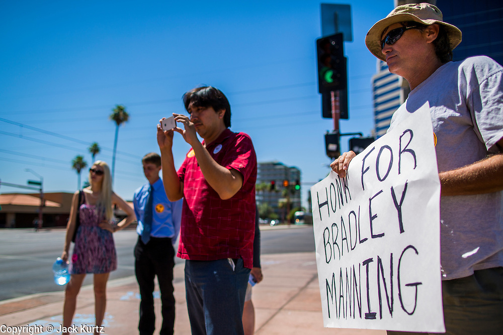 """06 JUNE 2012 - PHOENIX, AZ:   LEONARD CLARK, (right) a retired US Army soldier and Iraq War veteran, and others at a vigil in support of US Army PFC Bradley Manning in Phoenix. About 10 people gathered on a street corner in central Phoenix Wednesday to support Manning, who been criminally charged for passing secrets in the """"wikileaks"""" case and is awaiting trial in a US Army jail.       PHOTO BY JACK KURTZ"""