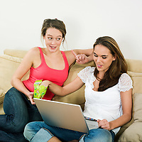 pictures in a living room of two young girls sitting on a couch looking at a laptop and eating sweets