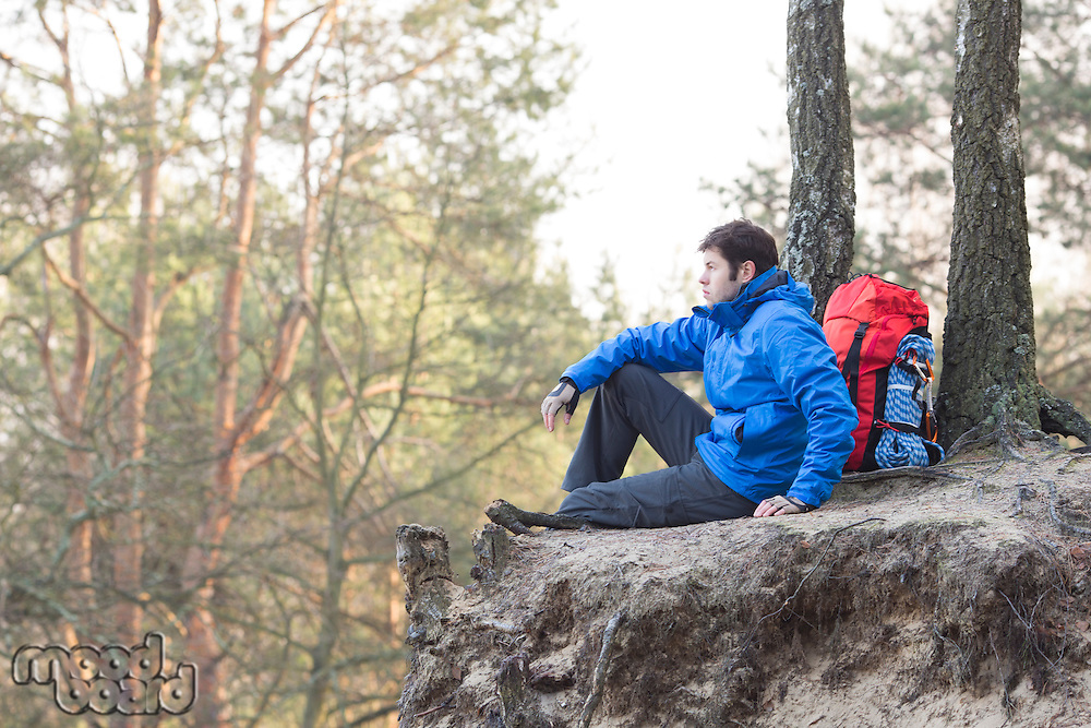 Side view of hiker sitting on edge of cliff in forest