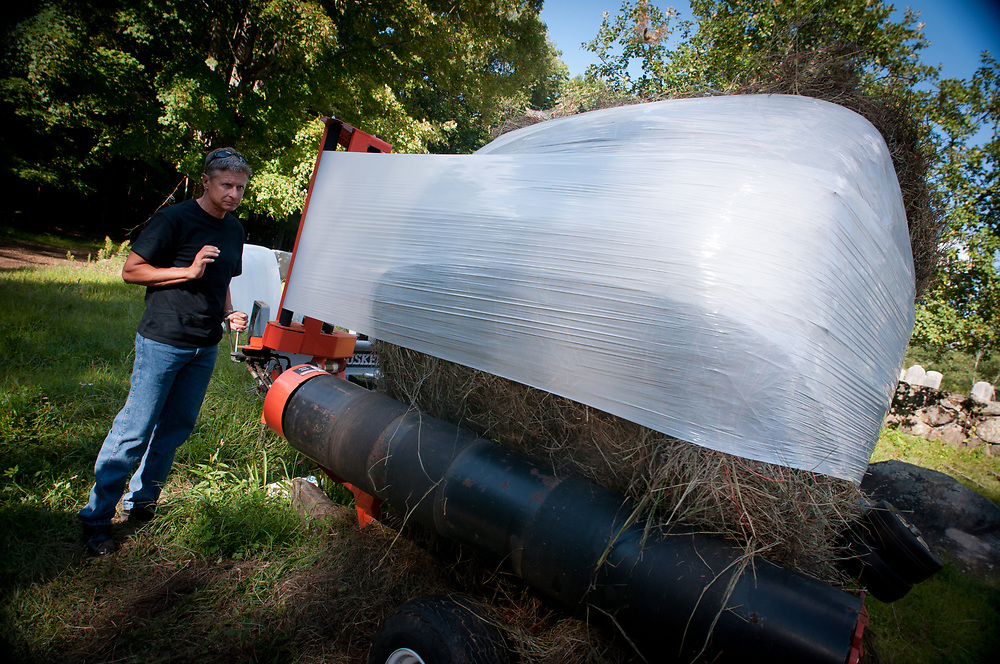 Presidential hopeful, former New Mexico Governor Gary Johnson learns how to wrap round bales of hay from Bruce Dawson at the Miles Smith farm in Loudon, NH. 23rd of august 2011.