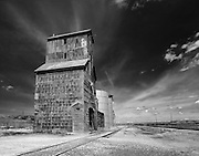 Abandoned grain elevator in Chugwater, Wyoming, sits next to unused railroad tracks