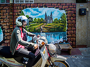 23 DECEMBER 2018 - CHANTABURI, THAILAND: A woman rides her motorcycle past a mural of the Immaculate Conception Cathedral in Chantaburi. Chantaburi is the capital city of Chantaburi province on the Chantaburi River. Because of its relatively well preserved tradition architecture and internationally famous gem market, Chantaburi is a popular weekend destination for Thai tourists.   PHOTO BY JACK KURTZ