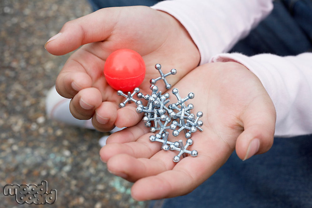 Boy (7-9) holding bouncy ball and jacks close-up