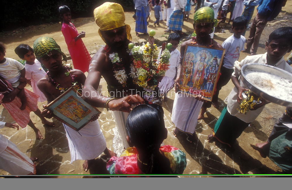 Thai Pongal Hindu festival on a tea estate. Man dressed as Lord Murugan applies holy ask to forehead.