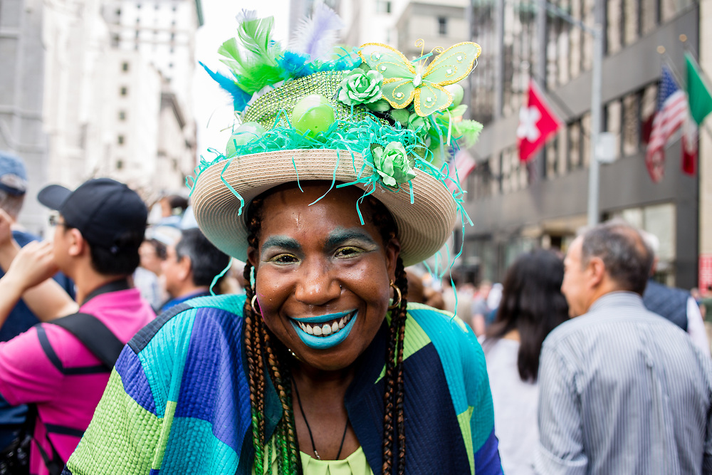 New York, NY - April 16, 2017. A woman with an elaborate hat with decorations of flowers and butterflies at New York's annual Easter Bonnet Parade and Festival on Fifth Avenue.
