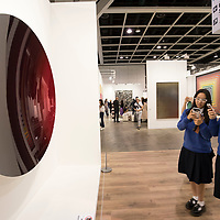 Visitors take a photo of artist Anish Kapoor's 'Mirror (Cobalt Blue to Magenta over Pagon Gold) 2016' at the Art Basel Hong Kong 2017 on 23 March 2017, in Hong Kong Convention and Exhibition Centre, Hong Kong, China. Photo by Chris Wong / studioEAST