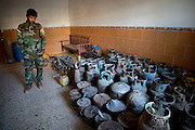 A Kurdish Peshmerga soldier views a stockpile of improvised explosive devices(IEDs) discovered in a civilians home. Bashiqa, Iraq. Nov. 20, 2016. (Photo by Gabriel Romero ©2016)