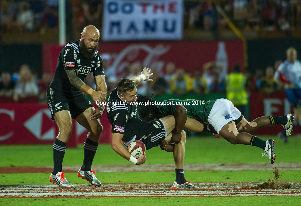 Tim Mikkelson of New Zealand is tackled by Branco du Preez of South African in the Cup Semi Final of the IRB Sevens World Series rugby tournament at the Emirates Airline Dubai Rugby Sevens in Dubai, UAE, on Saturday, Dec. 6th, 2014. Photo by: Stephen Hindley/Sportdxb/Photosport