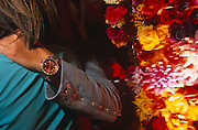 A man who is wearing a denim material jacket with studs sewn into the fabric and an expensive-looking wrist watch, drapes his arm over the shoulder of an unseen female at a glitzy couture party in London, for the fashion label Voyage. A large bouquet of flowers on the right are lit by a spotlight making their colours very bright and garish. The gathering was to celebrate the opening of the company's new store on the Fulham Road in a trendy area of Chelsea. It is an image of colourful (colorful) chic opulence and although  we see only the arm and back of two people and the slightly blurred flowers to the right, we imagine these people are wealthy and from privileged backgrounds.