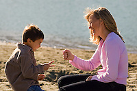 A Mom of Caucasian race and her son of mixed race play a hand game outside on the beach in autumn.