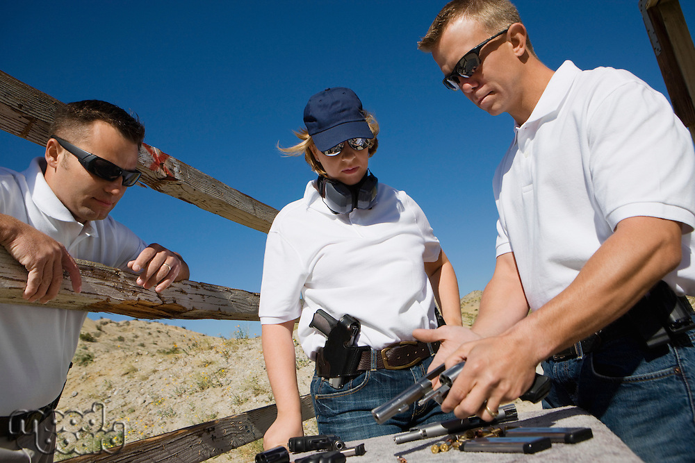 Instructor loading gun for man and woman at firing range