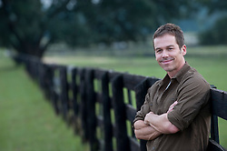 handsome man leaning on a fence outdoors
