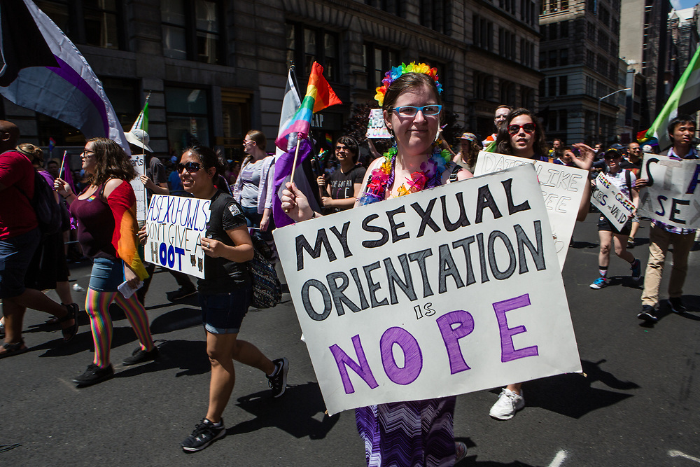 """New York, NY - 30 June 2019. The New York City Heritage of Pride March filled Fifth Avenue for hours with participants from the LGBTQ community and it's supporters. A woman with a group of asexual people carries a sign reading """"My sexual orientation is nope."""""""