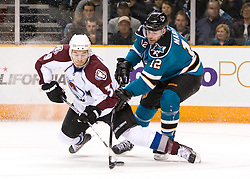 March 28, 2010; San Jose, CA, USA; Colorado Avalanche left wing T.J. Galiardi (39) and San Jose Sharks center Patrick Marleau (12) fight for a loose puck during the first period at HP Pavilion. San Jose defeated Colorado 4-3. Mandatory Credit: Jason O. Watson / US PRESSWIRE