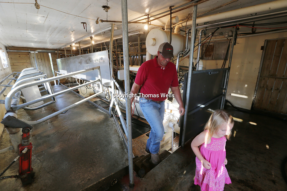 Jeremy Graham and his youngest daughter, Kendall, 4, leaving the milking station after a day of milking cows at their farm in Thaxton.