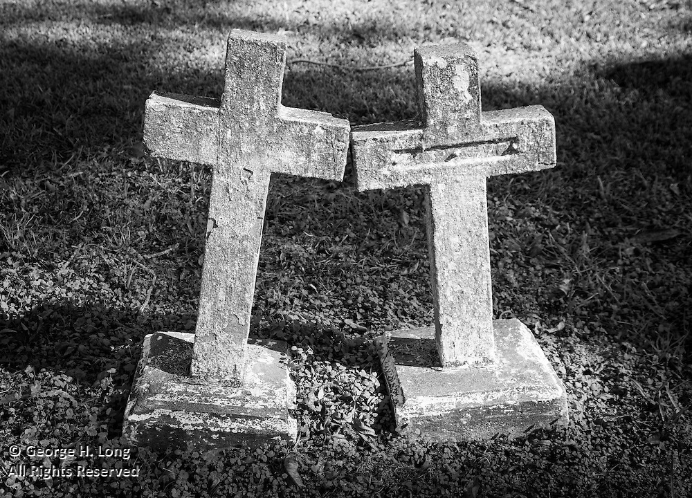 two stone crosses lean toward one another in St. Raphael Cemetery along River Road south of Plaquemine, Louisiana