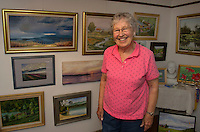 Gisela Langsten of the Lakes Region Art Association in her home studio with a backdrop of her oil and pastel paintings she has done depicting New England scenes as well as her various travel destinations through the years.  (Karen Bobotas/for the Laconia Daily Sun)