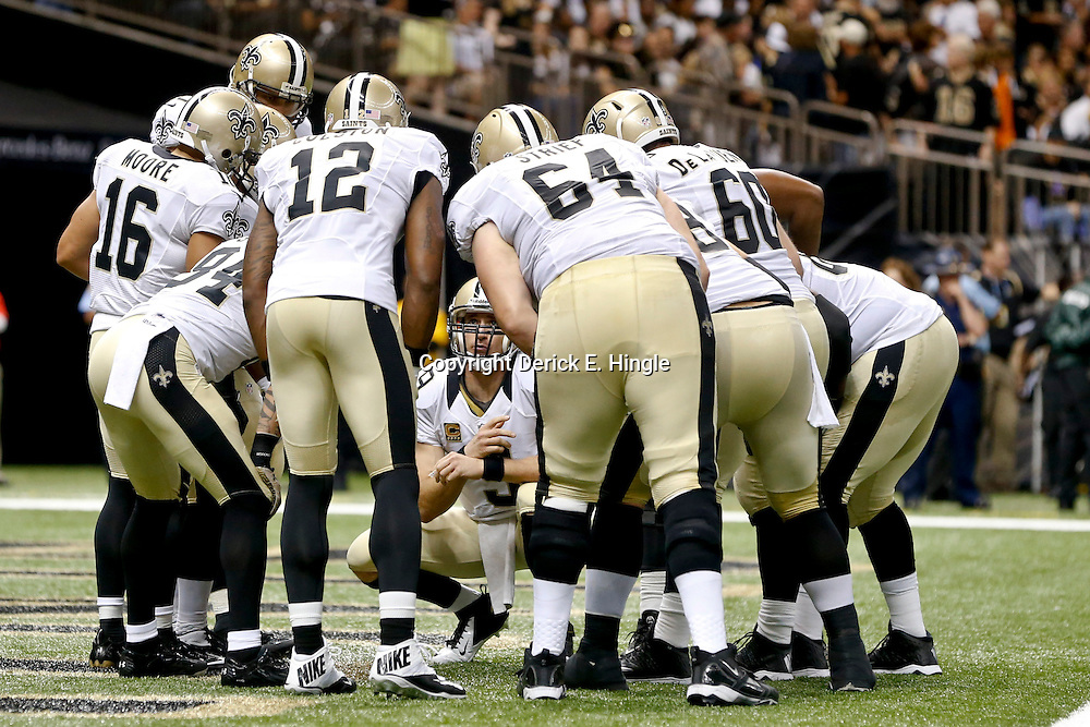 Sep 22, 2013; New Orleans, LA, USA; New Orleans Saints quarterback Drew Brees (9) huddles with teammates against the Arizona Cardinals during the first half of a game at Mercedes-Benz Superdome. The Saints defeated the Cardinals 31-7. Mandatory Credit: Derick E. Hingle-USA TODAY Sports