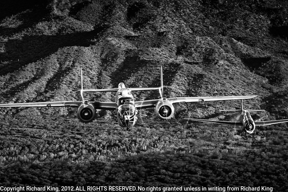 B-25 Mitchell and TBM Avenger flying in formation over Arizona desert in monochrome image