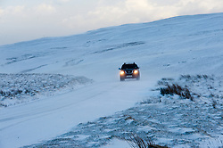 © Licensed to London News Pictures. 13/01/2017. Elan Valley, Powys, Wales, UK. Strong winds cause drifting of snow as vehicles negotiate the mountain road in the Elan Valley. Photo credit: Graham M. Lawrence/LNP