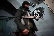 A Soldier of the Free Syrian Army passes a skull graffity at a wall in a makeshift headquarters of the FSA in Al Janoudiyah, Province of Idlib, Syria.