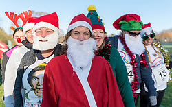 © Licensed to London News Pictures. 04/12/2016. London, UK. Runners in festive costumes take part in the Santa Dash in Cassiobury Park, Watford, raising funds for Mencap, a charity supporting people with a learning disability and their families.  This event is one of many Santa-inspired races taking place today across London raising funds for good causes. Photo credit : Stephen Chung/LNP