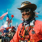Man with a trolley covered in flags, a cowboy hat and a sheriffs badge USA