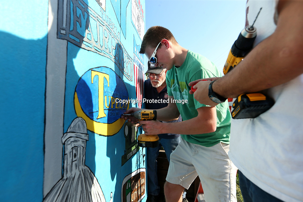 Aycock holds the extra drill as McNeal and Jerry Duckett install the mural on April 19 at the community garden on Spring Street in Tupelo.