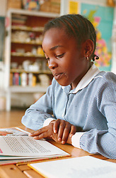 Junior school girl sitting at desk in classroom reading book,