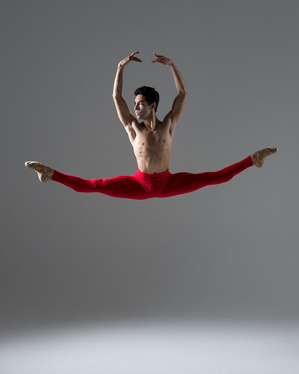 Classical male ballet dancer, Nicolas Moreno, jumping in the photo studio on a gray background. Photograph taken in New York City by photographer Rachel Neville.