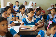 Girls dressed in school uniform attend a class