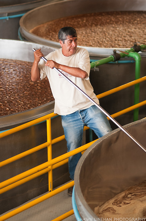 A worker at  La Cofradia distillery in Tequila, Mexico of Jalisco stirs the vats of fermenting tequila.