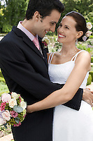 Mid adult bride and groom in garden embracing