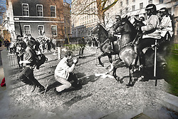 © Licensed to London News Pictures. 25/03/2020. London, UK. In this combined image police horses are seen in action outside the Ministry of Defence during the London poll tax riots on March 31st 1990 overlaid on the same location today. The protest on the last day of March in 1990 started peacefully when thousands gathered in a south London park to demonstrate against Margaret Thatcher's Government's introduction of the Community Charge - commonly known as the poll tax. Marchers walked to Whitehall and Trafalgar Square where violence broke out with the trouble spreading up through Charring Cross Road and on to the West End. Police estimated that 200,000 people had joined the protest and 339 were arrested. The hated tax was eventually replaced by the Council Tax under John Major's government in 1992.  Photo credit: Peter Macdiarmid/LNP