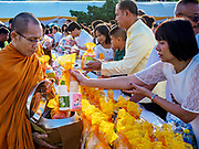 01 JANUARY 2019 - BANGKOK, THAILAND:   People make merit by presenting food to Buddhist monks and novices at the New Year's merit making ceremony on the plaza in front of City Hall in Bangkok. City Hall traditionally hosts one of the largest New Year merit making ceremonies in Thailand. This year about 160 monks participated in the event.      PHOTO BY JACK KURTZ