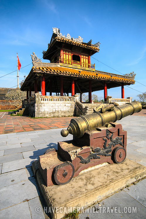 A restored pagoda and cannon at the Imperial City in Hue, Vietnam. A self-enclosed and fortified palace, the complex includes the Purple Forbidden City, which was the inner sanctum of the imperial household, as well as temples, courtyards, gardens, and other buildings. Much of the Imperial City was damaged or destroyed during the Vietnam War. It is now designated as a UNESCO World Heritage site.