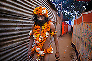 A Naga Sadhu, holding a digicam, walking down the narrow lanes of Juna Akhara during the Kumbh Mela, 2010. Naga Sadhus belong to the Shaiva sect, they have matted locks of hair and their bodies are covered in ashes like Lord Shiva.<br /> <br /> Kumbh Mela, 2010, Haridwar, Uttarakhand.